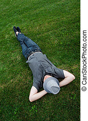 businessman lying in a field on green grass with the hat over his face. Passive income
