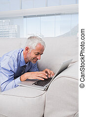 Businessman lying on couch using laptop and smiling