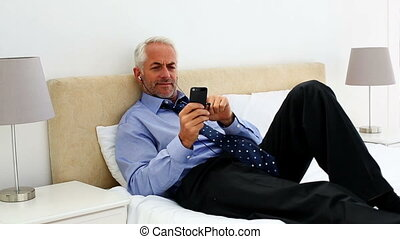 Businessman lying on his bed listen