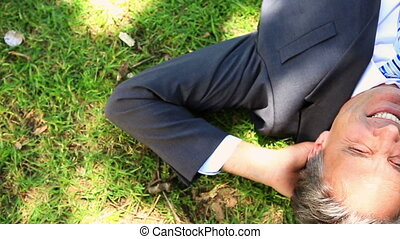Businessman lying on the grass