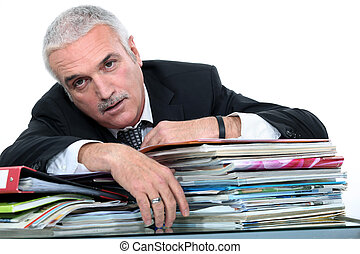 businessman lying over a pile of documents