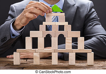 Businessman Making Building With Wooden Blocks
