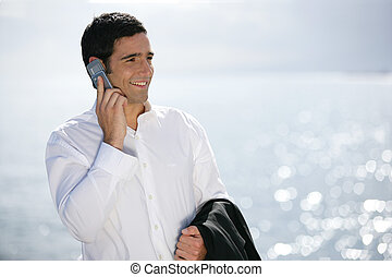 Businessman making call at the beach