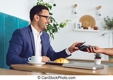 Businessman making contactless card payment in a cafe
