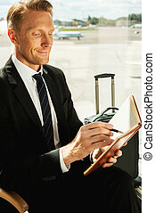 Businessman making notes. Side view of confident businessman in formalwear writing something in note pad while waiting for a flight in airport