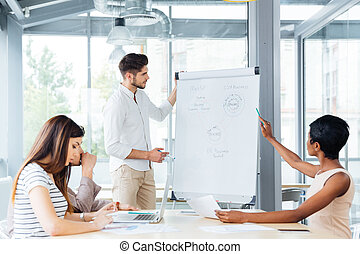 Businessman making presentation to colleagues on the meeting in office