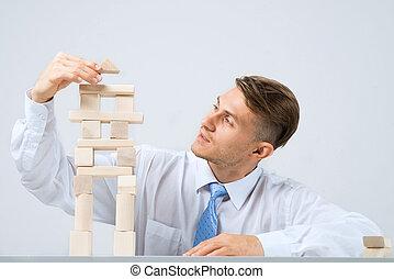 Businessman making tower