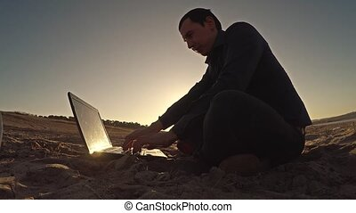 businessman man freelancer working behind sitting on beach laptop freelancing silhouette in the sun