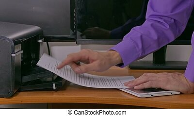 businessman man in office prints examines documents on printer typing on tablet