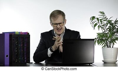 Handsome businessman manager playing game on laptop computer crossing fingers to win. Losing sitting down in frustration begins to hit table. Slow motion. Guy in suit, shirt, glasses. White background