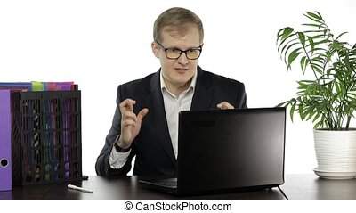 Handsome businessman manager playing game on laptop computer crossing fingers to win. Losing sitting down in frustration begins to hit table. Copy space. Guy in suit, shirt, glasses. White background
