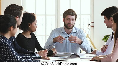 Corporate leader businessman chief boss manager talking at diverse group workshop meeting teaching instructing multiethnic workers presenting project plan training employees team sit at office table