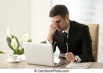 Businessman massaging nose bridge, holding glasses, eye strain,