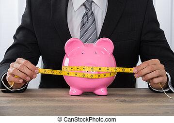 Businessman Measuring Piggybank On Desk