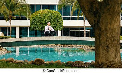 Businessman Meditating Doing Yoga Outside Office Building -...