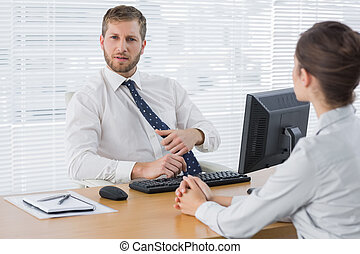 Businessman meeting with a colleague at his desk