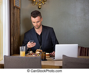 Businessman Messaging On Mobilephone While Having Meal In Cafe