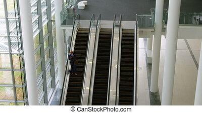 Businessman moving down from escalator 4k - Businessman...