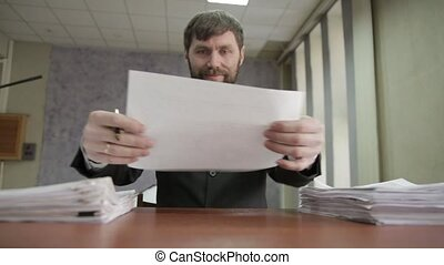 Businessman nervously signing and stamping incoming documents. office worker scatter documents around