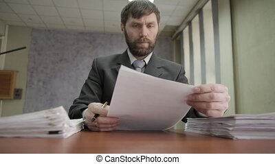 Businessman nervously signing and stamping incoming documents. office worker scatters documents around