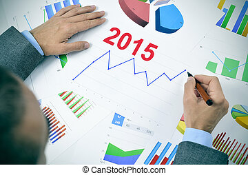 businessman observing a chart with an upward trend during...
