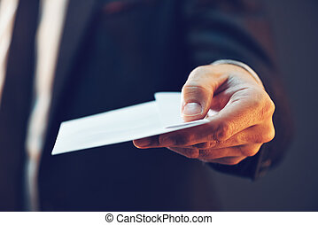 Businessman offering cash money in envelope as bribe,...