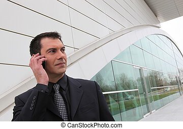 Businessman on a cellphone outside a modern building