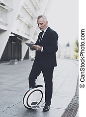 Businessman on a monowheel is searching on a tablet.