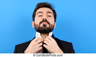 Businessman on blue background arranges his tie