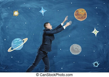 Businessman on blue chalkboard background trying to grasp a drawn planet among many others.