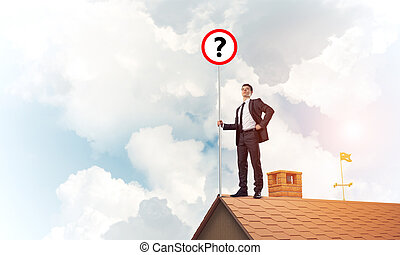 Businessman on brick house roof showing banner with question mar