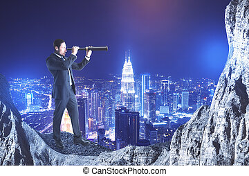 Businessman on cliff looking into distance