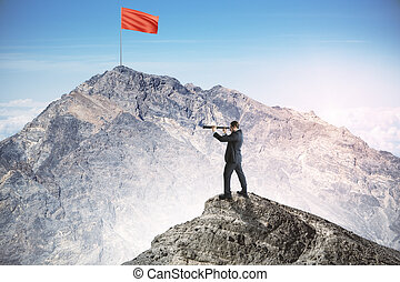 Businessman on cliff looking into the distance and red flag.