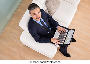Businessman On Couch Using Laptop