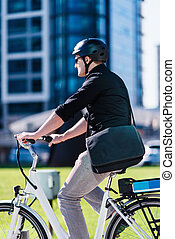 Businessman on electric bicycle in business center