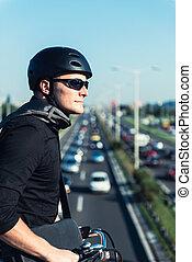 Businessman on electric bicycle standing on bridge