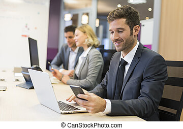 Businessman on mobile phone in office, sms, message