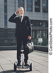 Businessman on mono-wheel speaks on the phone. - Man in a...