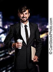 Businessman on night cityscape background