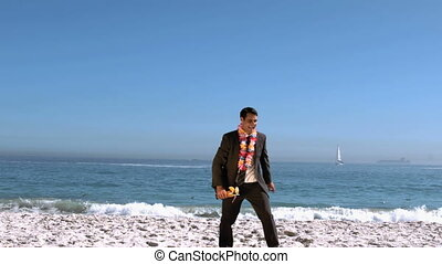 Businessman on the beach throwing