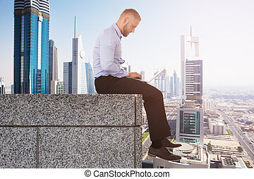 Businessman On The Edge Of Roof Using Laptop