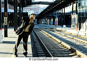 A businessman talking on the phone while waiting for the train