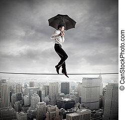 Businessman on tightrope with umbrella