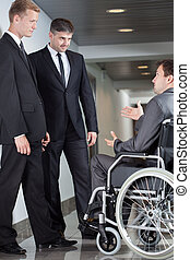 Businessman on wheelchair during small talk with his colleagues