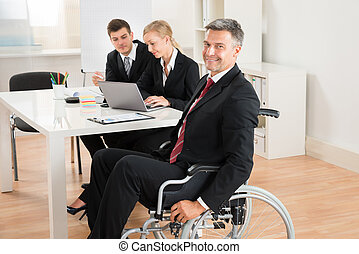 Businessman On Wheelchair With Colleagues In Office