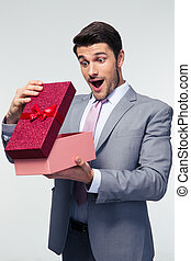 Businessman opening gift box - Handsome businessman opening...