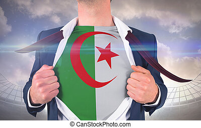 Businessman opening shirt to reveal algeria flag against large football stadium under cloudy blue sky