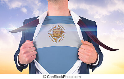 Businessman opening shirt to reveal argentina flag against beautiful orange and blue sky