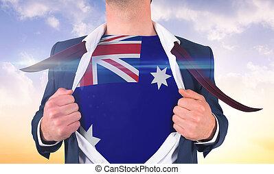Businessman opening shirt to reveal australia flag against beautiful orange and blue sky