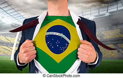 Businessman opening shirt to reveal brasil flag against large football stadium with lights